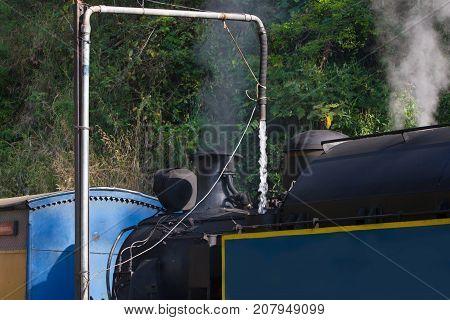 Steam train. Nilgiri mountain railway. Water refueling. India. Narrow-gauge Historical locomotive