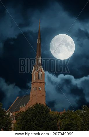 A red plaster steeple with bell and clock tower rising from trees into a night sky with moon