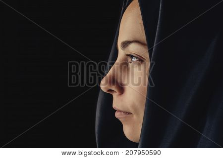 Muslim woman in hijab, close up portrait. European young girl in hijab looks forward, view from side, copy space, toned