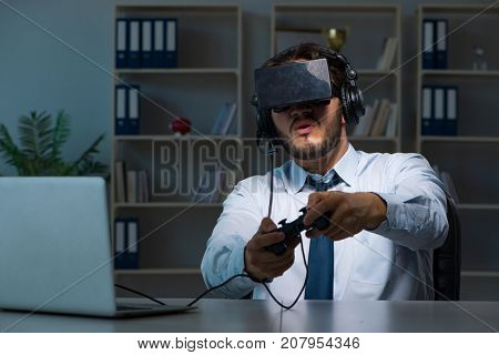 Businessman gamer staying late to play games