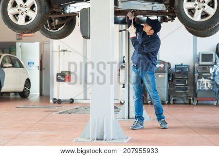 Mechanic fixing a lifted car