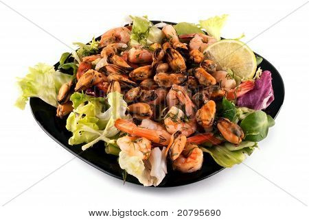 A salad with seafood on a black plate