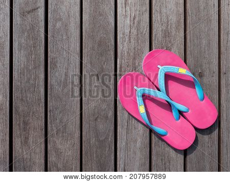 Pink flip flop / pink slipper on wooden floor on top view with sunlight in the afternoon