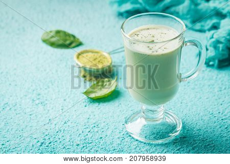 Green tea matcha latte in a glass cup on blue background. Concept of a healthy diet, superfood, antioxidant, cleansing