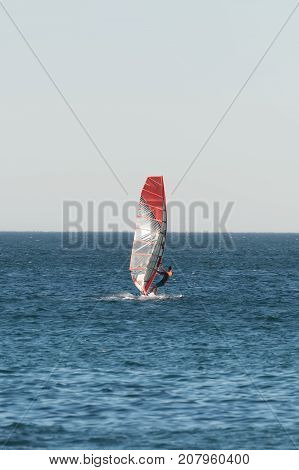 Unknown man windsurfing in the open sea.