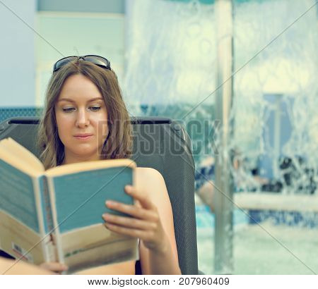 Woman reading a book near the water pool.
