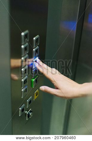 Woman pressing button inside the elevator.  Lift.