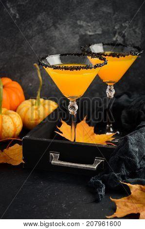 Fall seasonal cocktail Pumpkin Martini or Pumpkintini with black salt rim, selective focus.