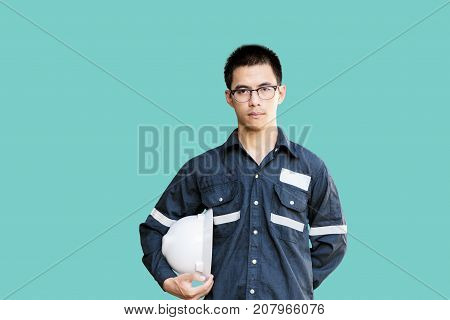 Asian manEngineer or Technician in white helmet glasses and blue working shirt suit holding safety helmet isolated on green mechanic and Oil and Gas industrial concept with clipping path.