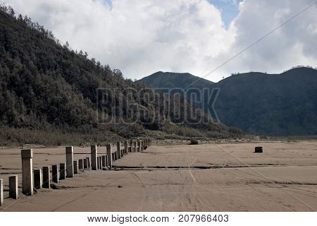 Grey poles sticking out of the volcanic brown sand landscape at the foot of the active Volcano mount Bromo at the Tengger Semeru National Park in East Java Indonesia.