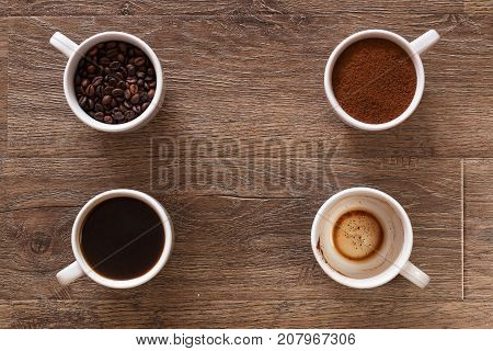 Variety of cups of coffee and coffee beans on old wooden table. Four cups of coffee, phases of drink - bean, ground and empty cup