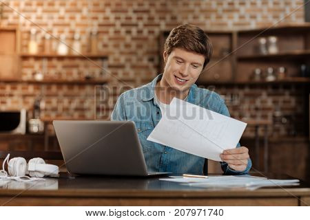 Content with result. Charming joyful young man sitting at the table, holding a printout with a blueprint and looking at it with a smile