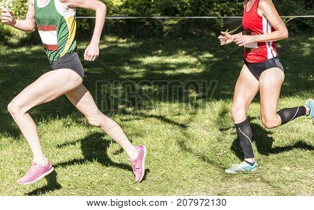 A female high school cross country runner in first place is being chased by the runner in second place but her form is so perfect that she wins easily.