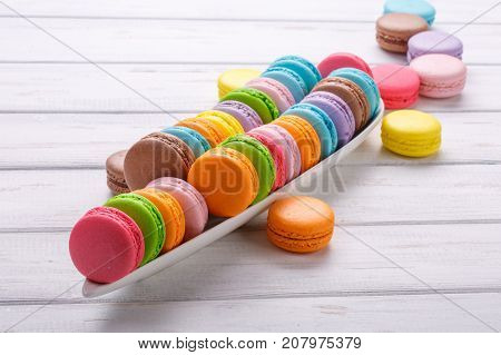 Sweet and colourful french macaroons lined in the shape of a crocodile on white wooden background