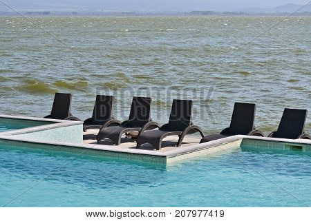 Swimming pool by the lake and sunbeds in a windy summer day