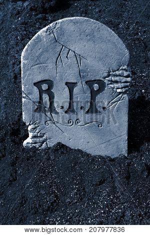 Halloween tombstone and skeleton in graveyard