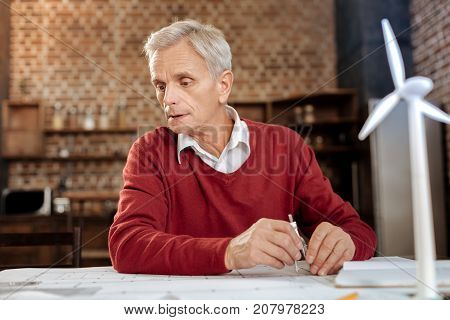 Experienced professional. Grey-haired senior man sitting at the table, holding a pair of compasses to draw a blueprint and looking intently at one of its parts