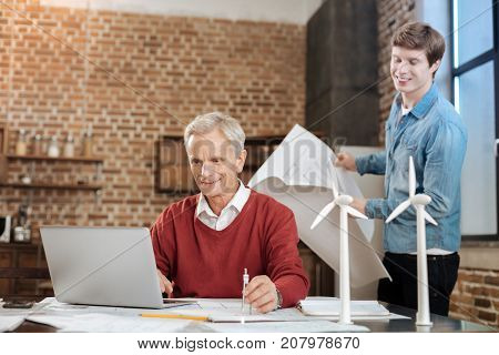 Pleasant ambience. Cheerful young man holding a blueprint and watching his senior colleague work on a laptop while holding a compass in his hand