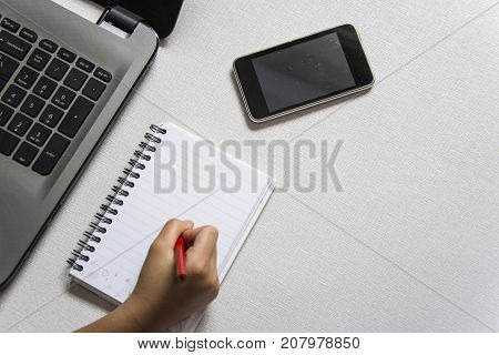 Top view of hand writing on a blank notebookwith laptop and smartphone. Office desk table with laptopsmart phonepencil and notebook.Flat lay photo.Top view with copy space.Office supplies and gadgets on desk table.Working desk table concept.