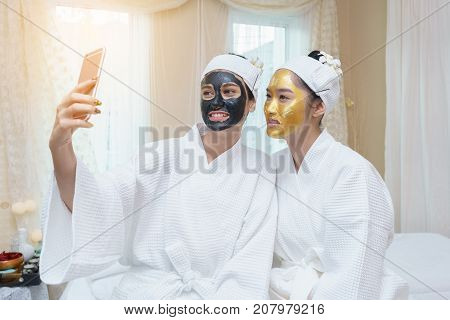 Beautiful young Asian woman having high quality facial mud mask and her friend who having high quality and authentic pure gold facial mask taking selfie after treatment in spa.