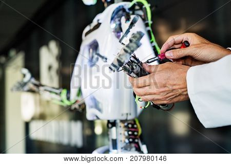 Unrecognizable scientist with a robot, mending or inventing.