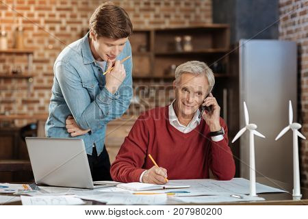 Crucial information. Pleasant young man standing near his senior colleague and peeking at the notebook of his colleague while he talking on the phone and making notes in it