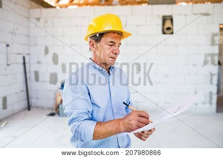 Senior architect or civil engineer at the construction site with blueprints, controlling issues at the construction site.