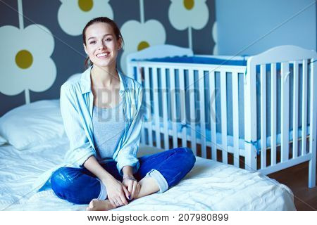 Young woman sitting on the bed near childrens cot. Young mom