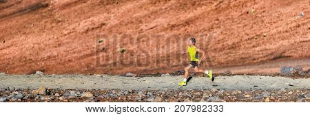 Man trail running in the mountain panoramic banner. Nature landscape background. Fit athlete runner doing sport exercise in nature. Ultra run training on path landscape background.