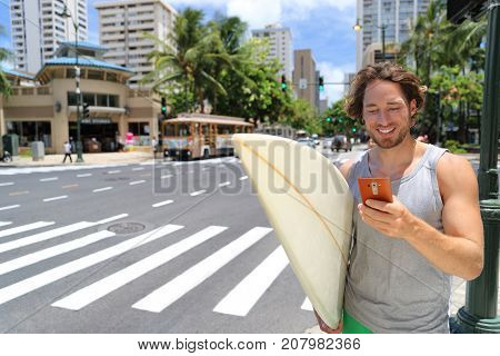 Hawaii surfer man Honolulu city lifestyle using smart phone going to Waikiki beach surfing holding surfboard on street. American living in USA.