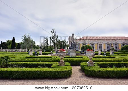 Queluz Portugal - June 3 2017. Neptune gardens (baroque) and the facades of the Queluz Royal Palace. Formerly used as the Summer residence by the Portuguese royal family