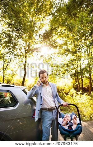 Young father carrying his little baby in a car seat, going into the car. Man with a smartphone making a phone call.