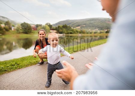 Cute little boy making first steps in nature. Young family spendind time in nature. Summer time.