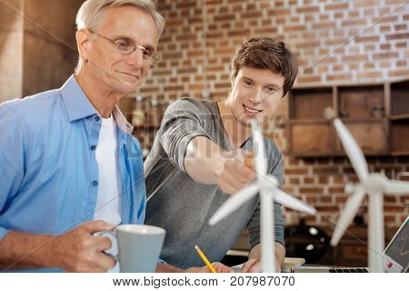 Smart remark. Pleasant young man pointing at a wind turbine model and making a remark about it while his mentor listening to it and smiling with approval