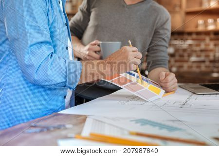 Quick choice. The close up of hands of a man pointing at a yellow color on a color chart with a pencil while discussing the choice with his colleague drinking tea