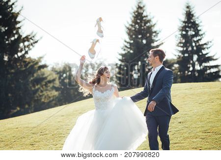 Happy and smiling newlyweds running outdoors holding hands. Close-up