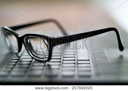blurred illustration of a glasses on a computer keyboard