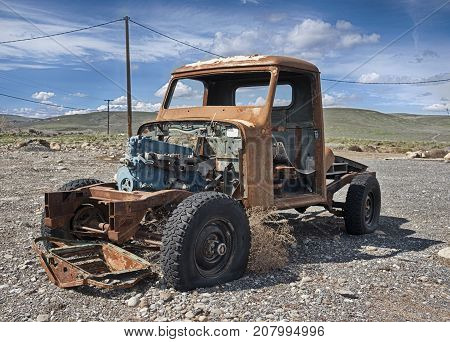A solitary old pickup truck abandoned in a gravel parking lot and exposed to the elements in Eastern Washington is rusting while being scavenged for parts.
