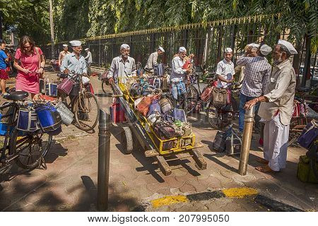 MUMBAI, INDIA - NOVEMBER 10, 2016: In Mumbai, a well-known logistics system delivers lunches through the streets. A dabawalah with a fully loaded hand cart sets off on his journey to deliver lunches from the Mumbai train station to offices and shops.