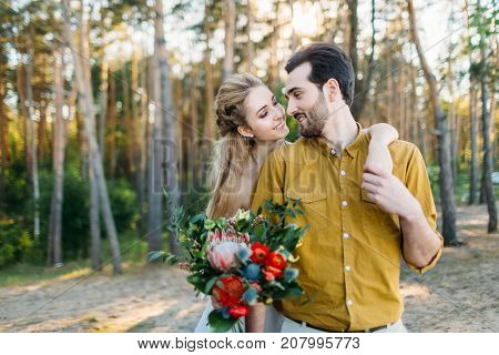 Beautiful bride embraces her groom by the shoulder. Wedding walk in a forest. A newlywed looks at each other. Girl in white dress and man in an olive shirt. Artwork., close-up