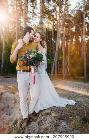 Beautiful bride embraces her groom by the shoulder. Wedding walk in a forest. A newlywed looks at each other. Girl in white dress and man in an olive shirt. Artwork., full length