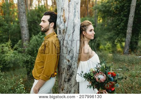 Bride and groom lean on the tree from different sides. Newlyweds are walking in the forest. Artwork,