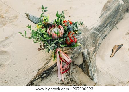 Rustic wedding bouquet with pink ribbons on the log, on the beach. Close-up. Outdoors. Artwork, grain