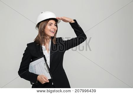 Portrait of a cheery young woman in hard hat and suit looking far away with hand on her forehead while standing and holding clipboard with documents isolated over white background