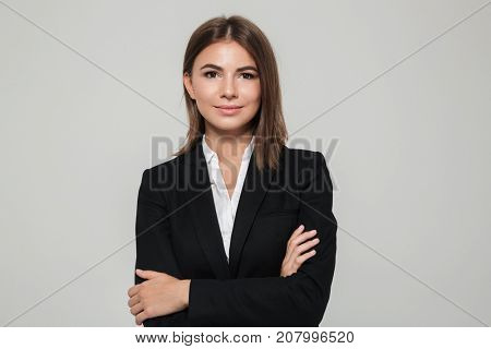 Portrait of a confident young businesswoman in suit with arms folded looking at camera isolated over white background