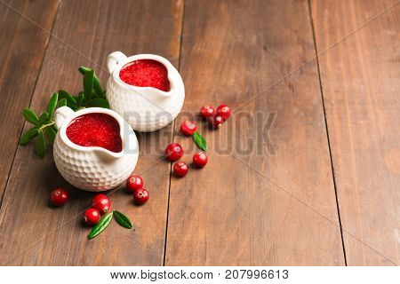 Cranberry Sauce In Ceramic Saucepan Over Wooden Background