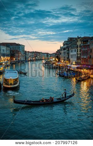Grand Canal with gondola at night in Venice, Italy. Grand Canal is one of the major water-traffic corridors in Venice.