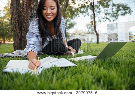 Close-up of pretty asian student with charming smile, keeping records in paper notebook while studying online with laptop, sitting on grass, outdoor