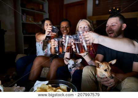 group of friends sitting on couch making cheers with beer