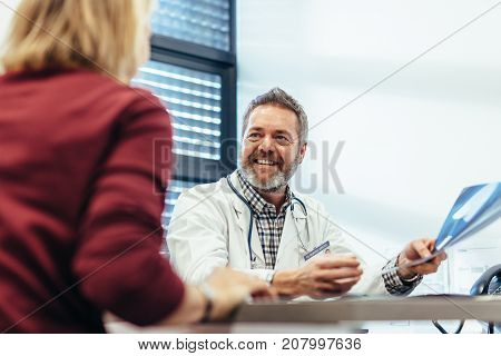 Happy medical doctor showing diagnosis of x-ray image to female patient sitting at office desk. Doctor holding medical scan results and giving good news to his patient.